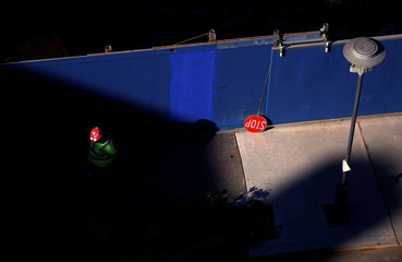 A worker stands next to a stop sign on a construction site for a residential apartment block in central Sydney