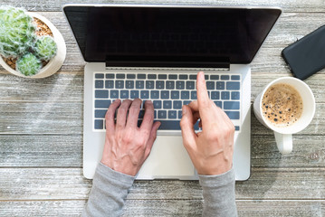 Person working on a laptop computer overhead view on a wooden desk
