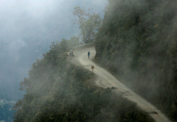 """A competitor runs during the Bolivia Sky Race on the """"Death Road"""" from Yolosa to Chuspipata, near La Paz"""