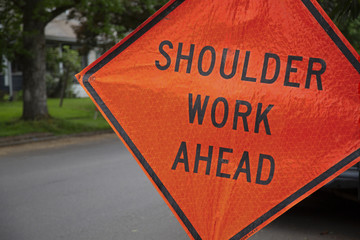 "Orange and Black ""Shoulder Work Ahead"" Sign in Residential Neighborhood, Daytime"