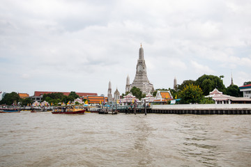 Wat Arun buddhist temple . famous ancient grand palace in Bangkok Thailand , asian travel landmark . old historic architecture . Chao phraya river with boats . beautiful clear sky and clouds