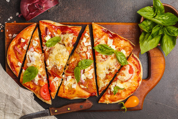 Oval homemade pizza with feta cheese, tomatoes and basil on a wooden board.