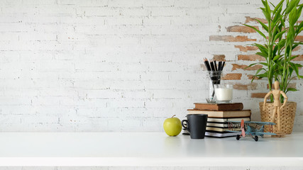 Loft workspace with books, coffee mug and copy space over white brick wall.