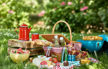 Picnic basket next to small grill and wooden box