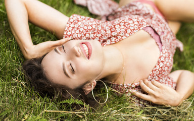 Beautiful Girl lying on the Field.Green Grass. Happy and Smiling.