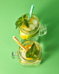 Citrus fruits slices of lemon and lime, ice, water and plastic straws in the glass on a green background. Two glass jars with a cold natural handmade lemonade with bubbles of air. Top view.