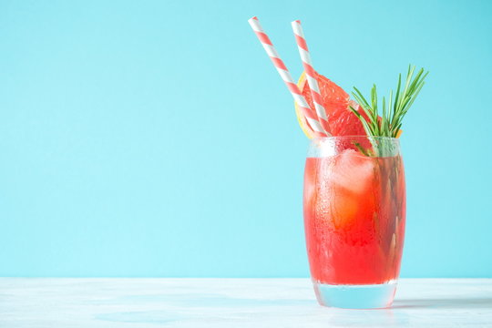 Refreshing cocktail of grapefruit with ice and rosemary on colored background of mint. Healthy citrus summer drink.