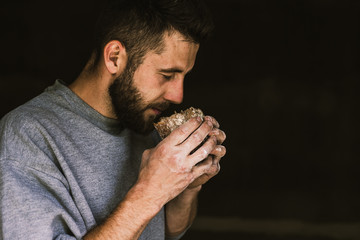 Fototapeta Close up of a young bearded man smelling delicious freshly baked bread