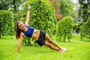 Poster Ecole de Danse Beautiful brunette female fitness girl exercising outside in a leafy and green city park. Lady in sports top jogging in park. Healthy girl lifestyle background with copy space