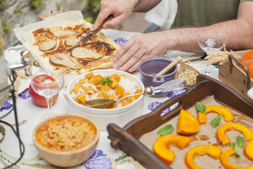 rice with pumpkin and honey on the table and other autumn food, pie with pear. Delicious family dinner in the courtyard. Men's hands cut the cake. Copy space