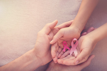 Adult and child hands holding pink ribbons, Breast cancer awareness, abdominal cancer awareness and October Pink background