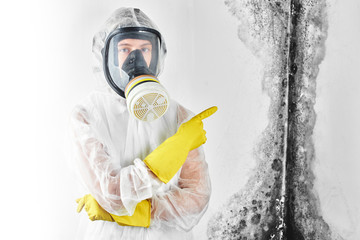 A professional disinfector in overalls and a mask points a finger at the black mold on the wall. Removal of the fungus in the apartment and house. Aspergillus..