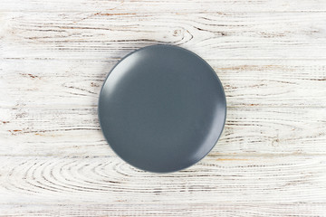 Top view of blank dish on a wood background