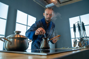 A man is mixing a spoon of coffee in a copper turkey