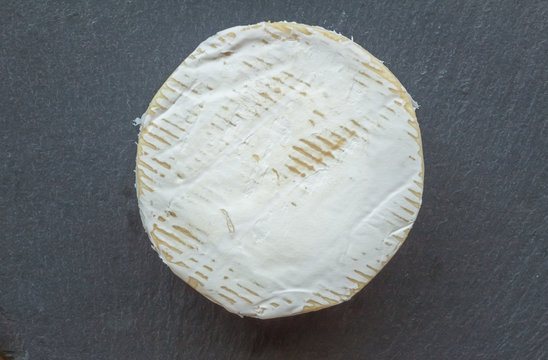 Camembert cheese isolated on black slate cheese board - Top view photo