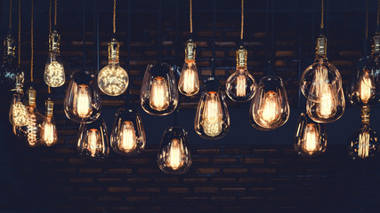 Foto auf Acrylglas Retro Beautiful vintage luxury light bulb hanging decor glowing in dark. Retro filter effect style.