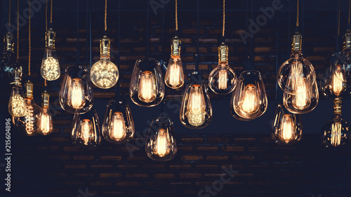 Wall mural Beautiful vintage luxury light bulb hanging decor glowing in dark. Retro filter effect style.