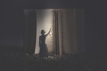 Curious woman illuminates with a lantern a giant book at night
