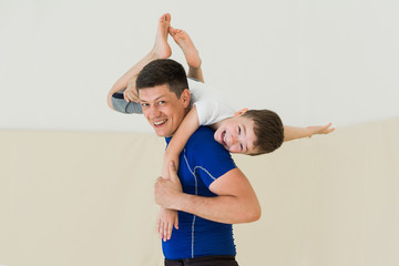 Dad and son training in gym together. Portrait of young father with little kid boy at sport training. child sits on father shoulders and hugs his neck, they smiling and laughing
