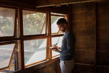Man writing note on diary at cabin