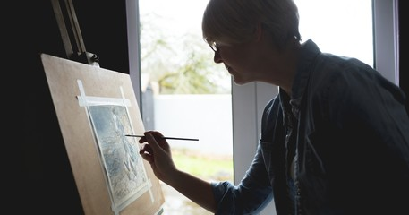 Female artist painting picture on canvas at home
