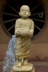 A statue of a monk carved from yellow stones.