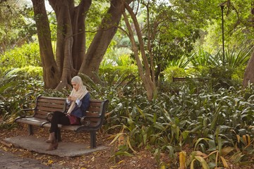 Hijab woman sitting on bench and using mobile phone