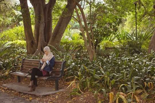 Young woman using smartphone while sitting on bench in park