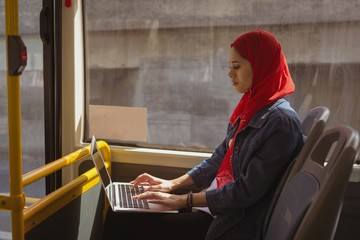 Hijab woman using laptop while travelling in bus