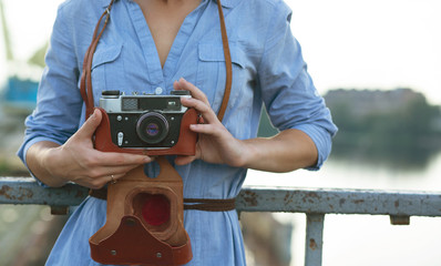 Beautiful hipster model photographer in blue dress holding vintage film camera.Space for text