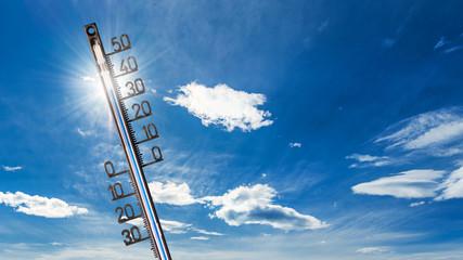 Hitzewelle-Hintergrund: Thermometer mit hohen Temperaturen, vor strahlender Sonne