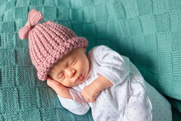 Cute newborn baby sleeps in a hat. Green wool clothes background.