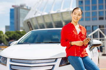 Digital age. Cheerful happy woman holding her smartphone while standing near the car