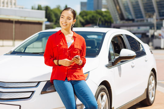 Car owner. Happy pleasant woman standing near her car while looking aside