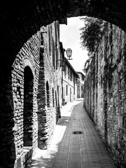 Picturesque medieval narrow street of San Gimignano old town, Tuscany, Italy. Black and white image.