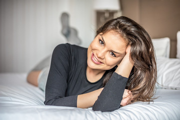 Happy beautiful young brunette woman relaxed smiling on bed .