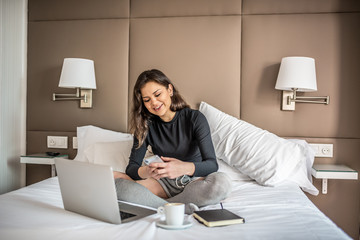 Happy beautiful young brunette woman relaxed smiling on bed on the mobile phone and computer working