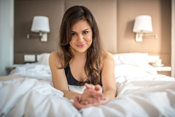 Happy beautiful smile thoughtful young brunette woman relaxed lying down on bed