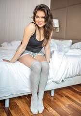 Happy beautiful smile thoughtful young brunette woman relaxed seating on the bed