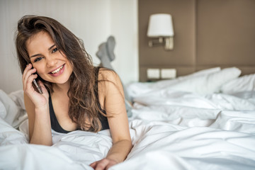 Happy beautiful young brunette woman relaxed smiling in bed on the mobile phone .