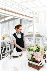 Girl waiter serves a table in the restaurant