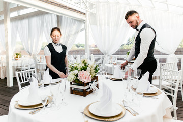 Two waiters serve a round table in the restaurant