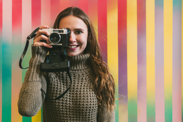 Happy young woman holding a vintage camera in a colorful background