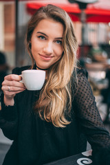 Portrait of a young beautiful blonde drinking coffee