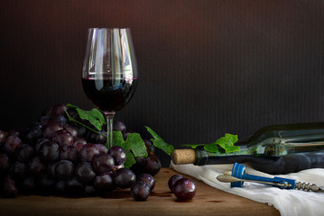 Glass of Wine with bunch of grape and wine bottle with wine opener on the wooden plank which has white cloth