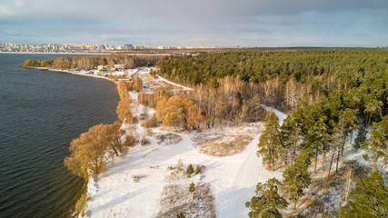 Aerial photo of city forest with pine trees in early winter near river, residential area on the background, Chelyabinsk, Russia