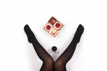 Creative photo of female legs in black pantyhose with a cup of coffee and a box of small cakes on a white background. Concept. Top view
