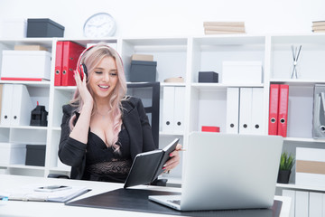 Beautiful girl in a black suit wearing headphones and working in the office