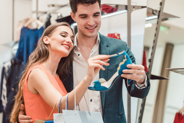 Woman with her man looking at blue shoes in store wanting them badly