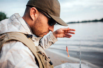 A picture of man sitting at the edge of water and looking down. He holds spoon with bait. Guy is preparing to fishing.